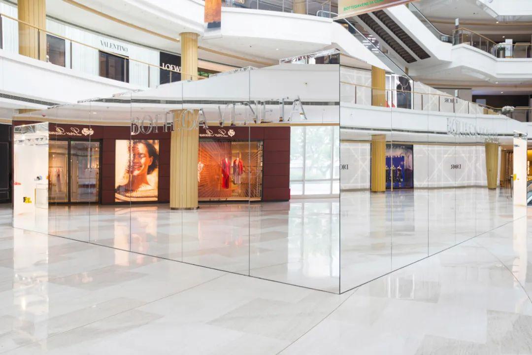 通體鏡面,將周圍的色彩和光線吸收又反射;坐落鬧市,隱身於繁華之中,自成一處,不做聚光燈的追尋者,更像是大千世界的反映者。 如果不是外部刻出的鏡面字體「Bottega Veneta」,你很難猜到,它就是 BV 所推出的全新限時精品店「隱市之店」(The Invisible Store)。